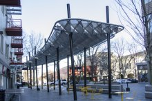 Banker Wire mesh forms a shade structure that serves as the centerpiece for the plaza, and meaningfully evokes Greenville's history.